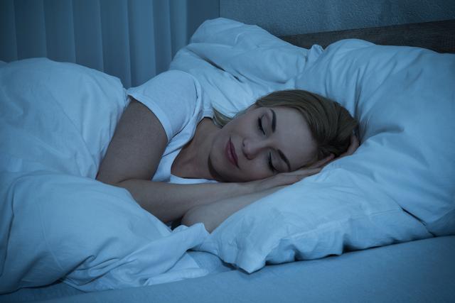 暗い部屋で眠る女性