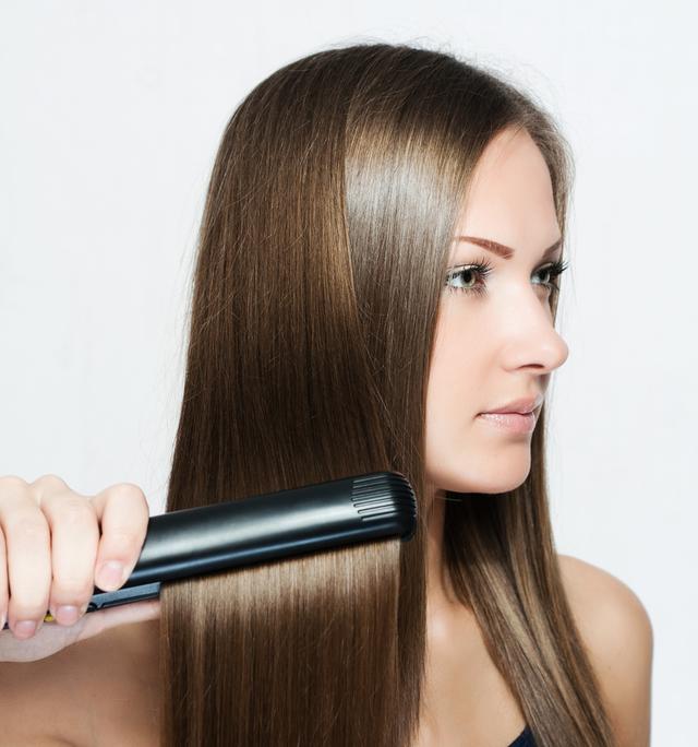 ストレートヘアアイロンを使う女性
