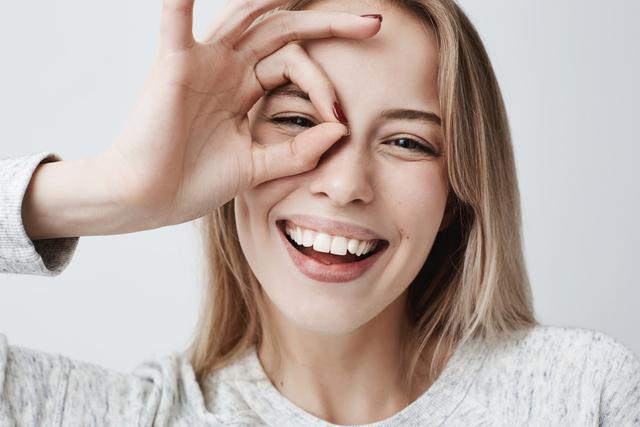 目の周りで指の丸をつくる女性