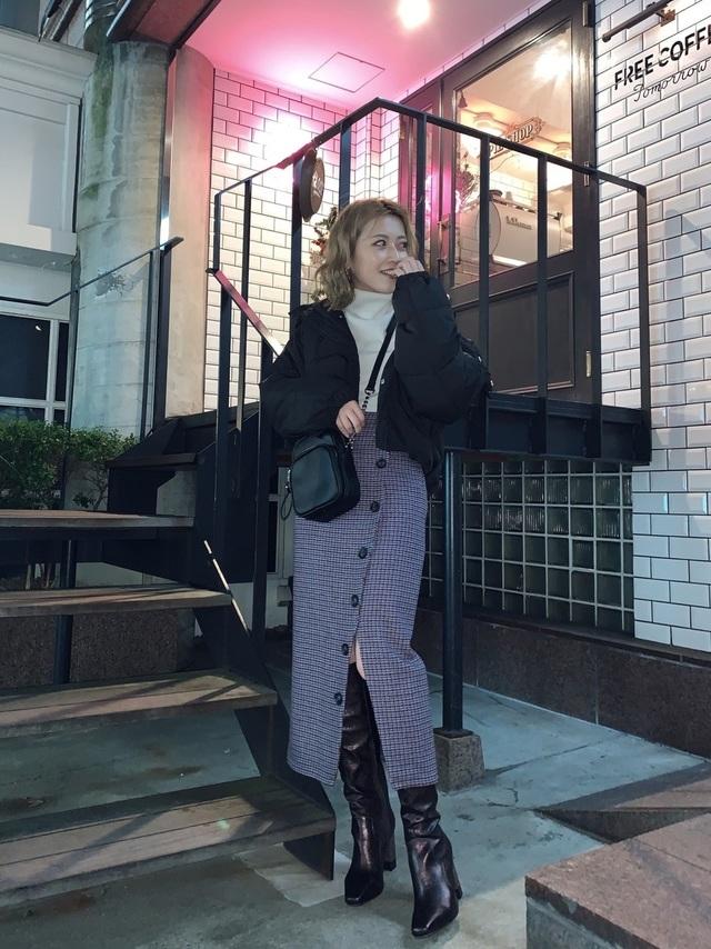 スリットタイトスカートにロングブーツを合わせた女性