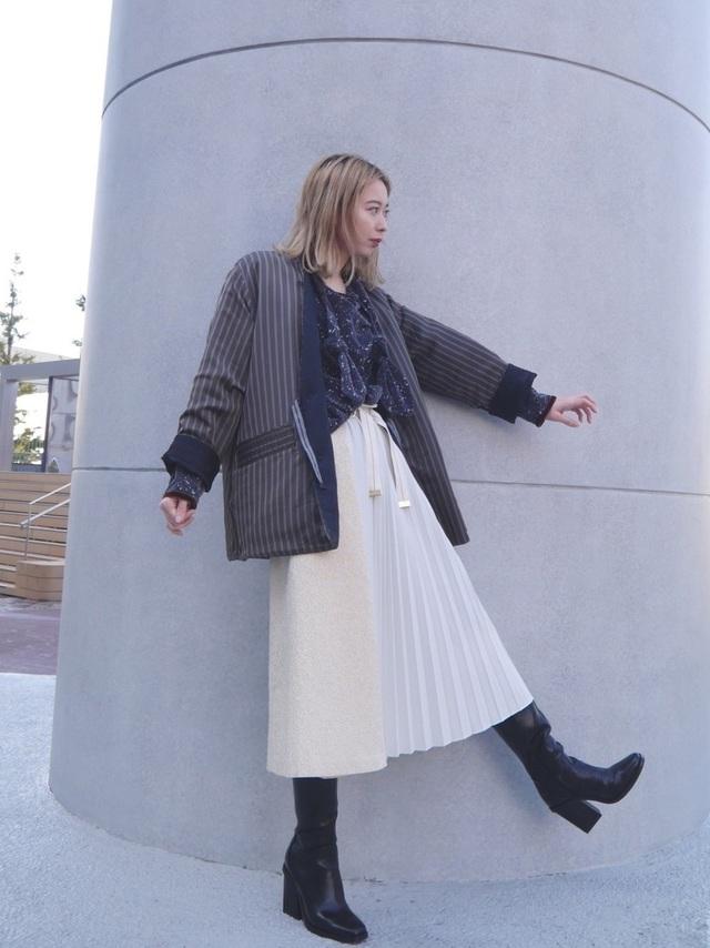 プリーツスカートにロングブーツを合わせた女性