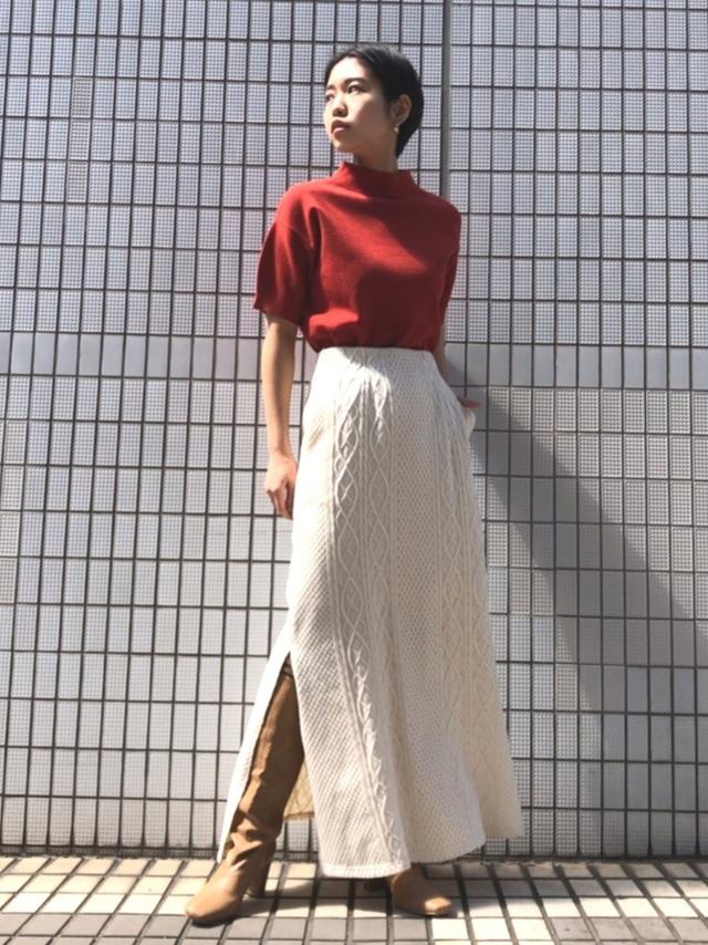 ニットスカートにロングブーツを合わせた女性
