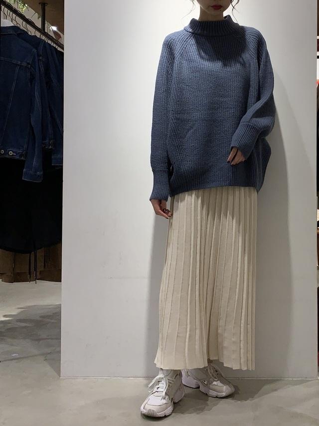 ホワイトのプリーツニットスカートを着た女性