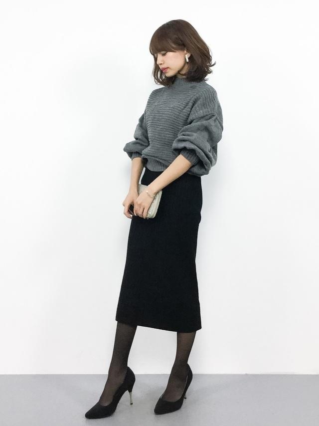 ブラックのタイトニットスカートとパンプスを着用した女性