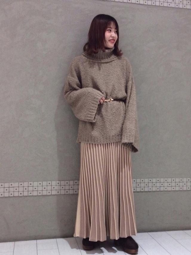 ベージュのプリーツニットスカートを着た女性