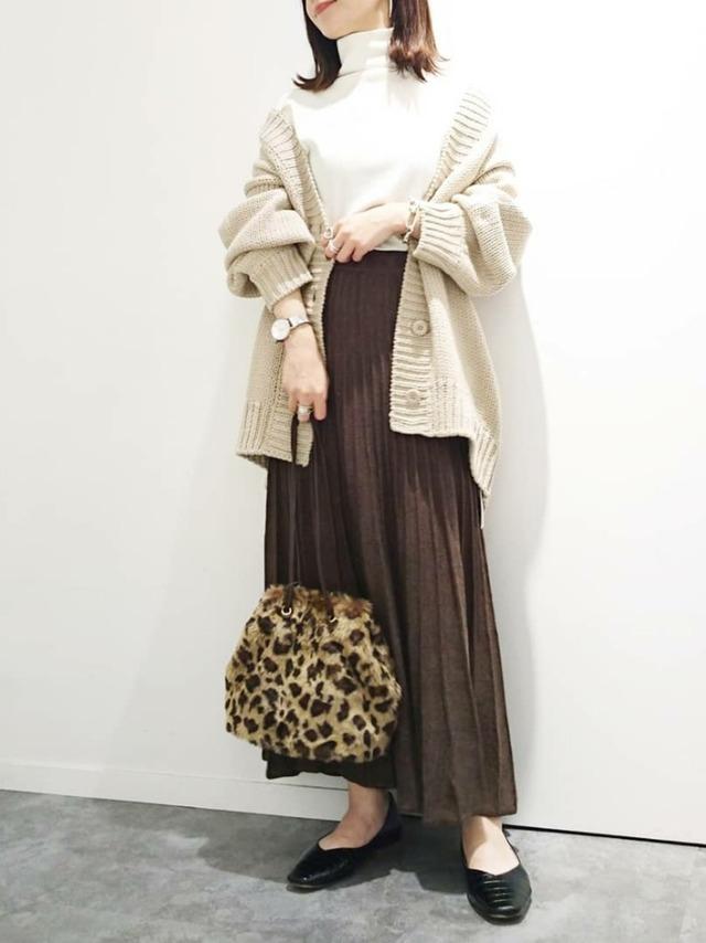 ブラウンのニットスカートとベージュのカーデを着用した女性