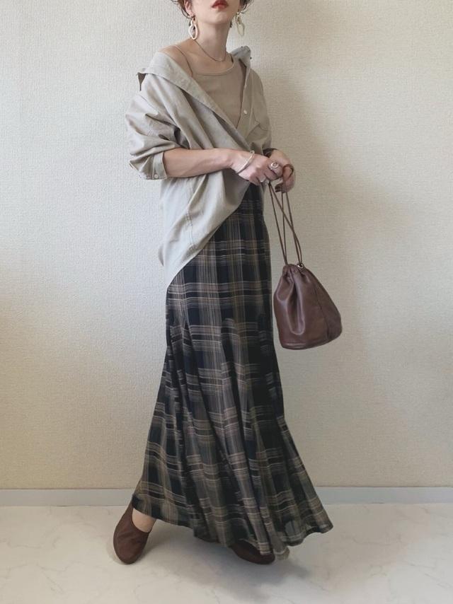 チェック柄スカートにシャツを合わせた女性