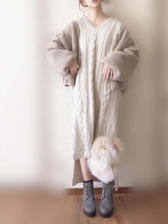 ケーブルニットワンピを着た女性